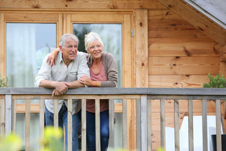 log: Senior couple standing oustide log cabin in countryside