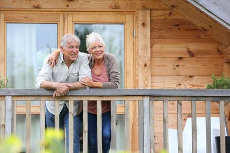 jubilados: Senior pareja de pie oustide cabaña de madera en el campo Foto de archivo