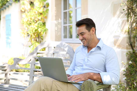 work addicted: Mature man on week-end working from home with laptop
