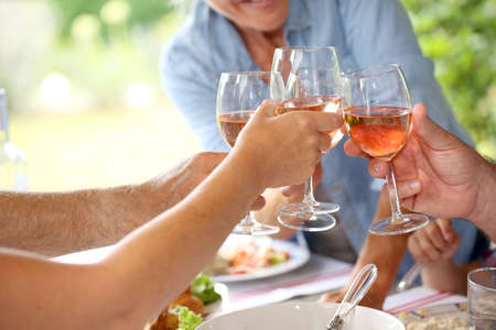 Closeup of wine glasses held by family at lunch photo
