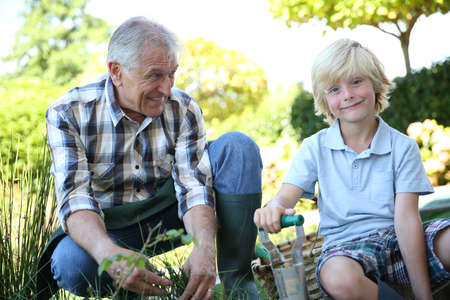 Grandpa with grandson gardening together in summer time photo