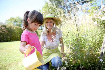 Woman with little girl watering plants in garden photo