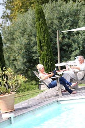 Senior couple in backyard reading book in deckchairs photo