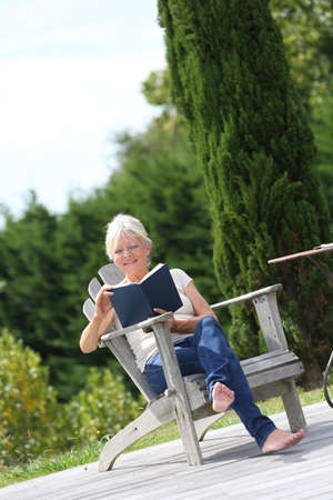 Senior woman reading book in backyard photo