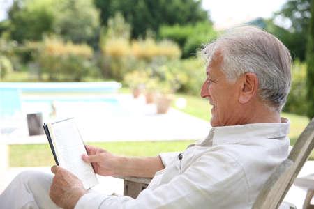 Senior man reading book in pool deck chair photo