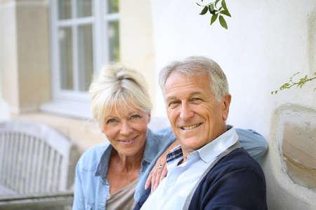 Senior pareja de relax en el banco junto a la casa Foto de archivo - 31993442