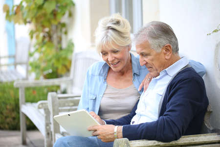 Senior couple websurfing on internet with tablet Stock Photo