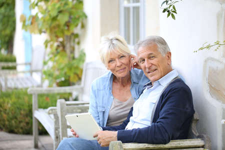Senior couple websurfing on internet with tablet photo