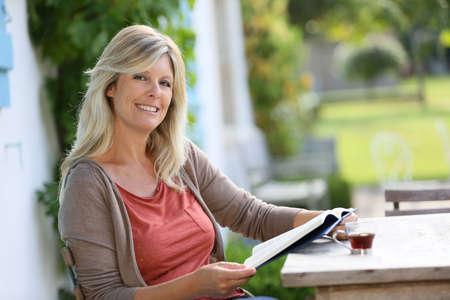 woman 40 years: Mature woman reading book in backyard