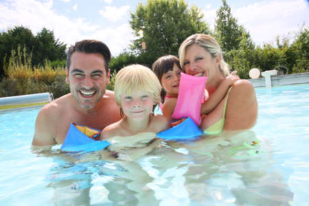Happy family enjoying swimming time in pool photo