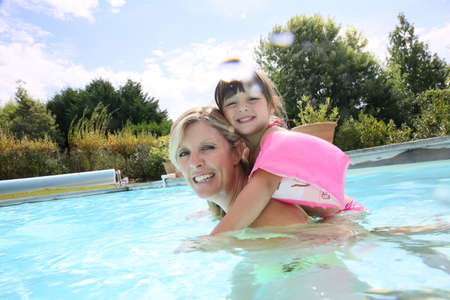 Mother and daughter playing in swimming-pool photo