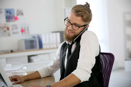 phonecall: Young designer in office talking on phone
