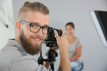 Portrait of young photographer working in studio photo