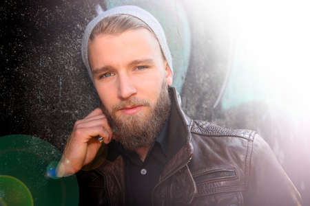 rebellious: Portrait of stylish guy with beard in street