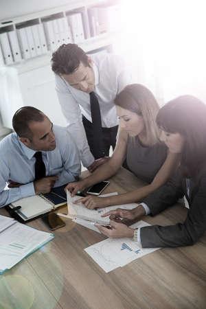 work meeting: Grupo de hombres de negocios reunidos alrededor de la mesa de la tableta wih