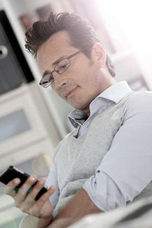 40 years old man: Relaxed businessman in office using smartphone