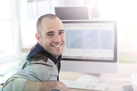 uomo felice: Ritratto di studente di fronte al computer desktop