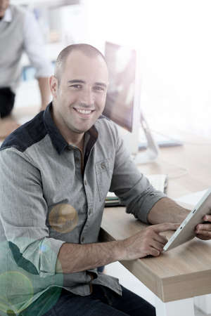 shaved: Young smiling man in training class using digital tablet