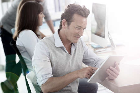 40 years old man: Attractive businessman in office using tablet Stock Photo