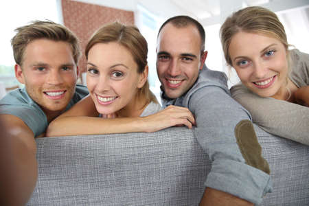 shared sharing: Cheerful roommates sitting in sofa at home