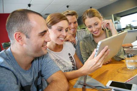 cafe internet: Grupo de amigos en el salón campus websurfing con la tableta Foto de archivo