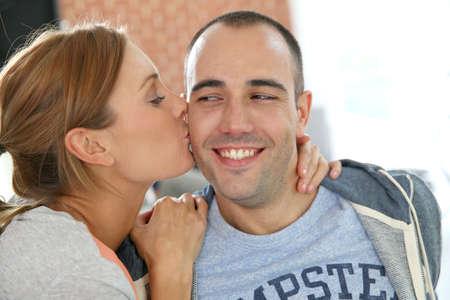 cheek: Girl kissing boyfriend on cheek Stock Photo