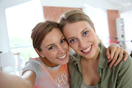 roommates: Cheerful girlfriends taking picture of themselves