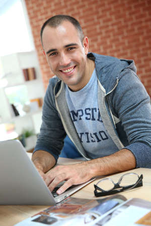 websurfing: Smiling man at home websurfing on net Stock Photo