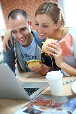 30 years old: Roommates eating sandwich in front of laptop Stock Photo