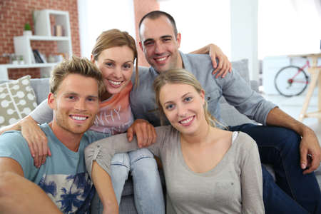 shared sharing: Roommates sitting together in couch Stock Photo