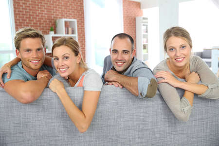 roommates: Cheerful roommates sitting in sofa at home
