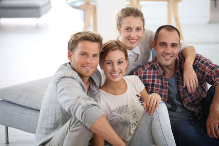 shared sharing: Group of young people sitting in shared apartment Stock Photo