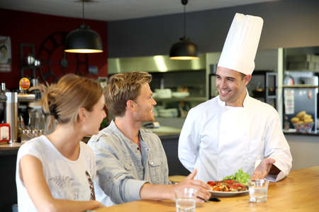Young chef serving cooked dish to customers Stock Photo
