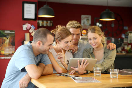 canteen: Students in campus lounge websurfing on tablet Stock Photo