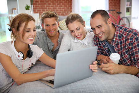 roommates: Group of friends having fun making a video call Stock Photo