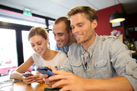 Young people in campus lounge connected on smartphone Stock Photo