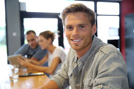 Portrait of trendy guy sitting in campus lounge