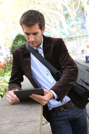 Businessman using digital tablet in city park photo