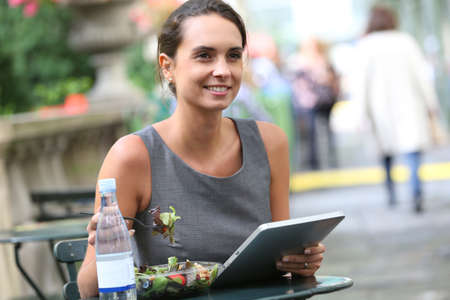 having lunch: Businesswoman working with tablet while having lunch Stock Photo