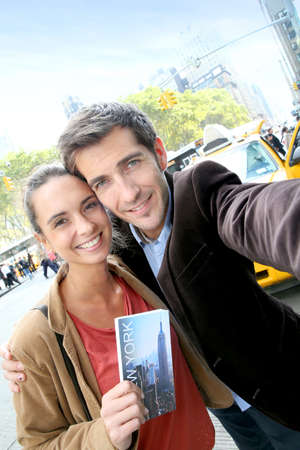 Couple in New York city taking picture with smartphone photo