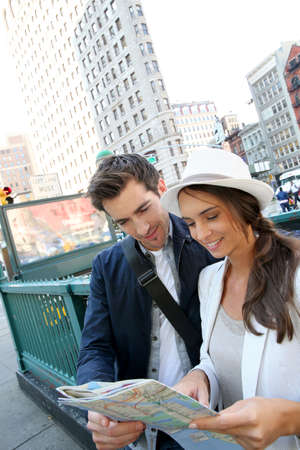 new york map: Couple looking at city map by the Flatiron buidling, NYC Stock Photo