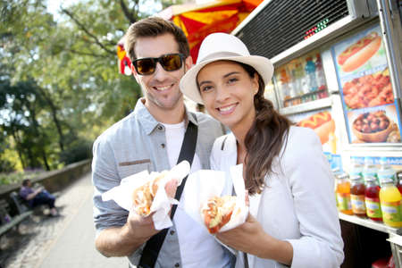 hot dogs: Tourists in New York city eating hot dogs