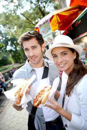street food: Tourists in New York city eating hot dogs