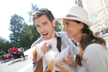 Tourists in New York city eating hot dogs photo
