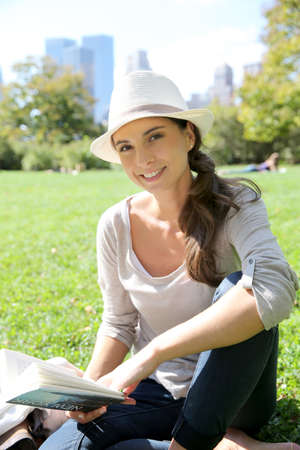 Cheerful woman in Central Park reading New York city guide photo