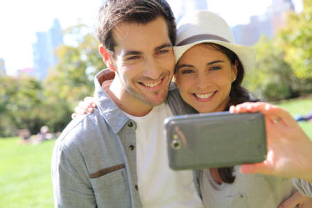 Cheerful couple taking picture of themselves in central park photo
