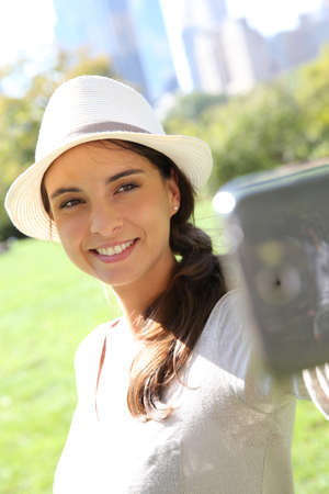 Beautiful woman with hat taking picture with smartphone photo