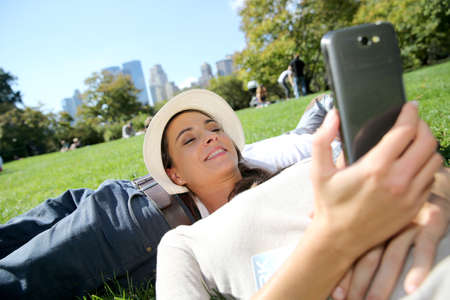 Woman relaxing on Central Park, using smartphone photo