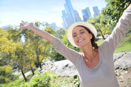 city park skyline: Cheerful girl in Central Park lifting arms up