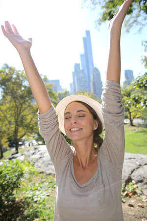 Cheerful girl in central Park lifting arms up photo